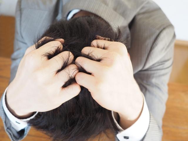 頭抱える男性
